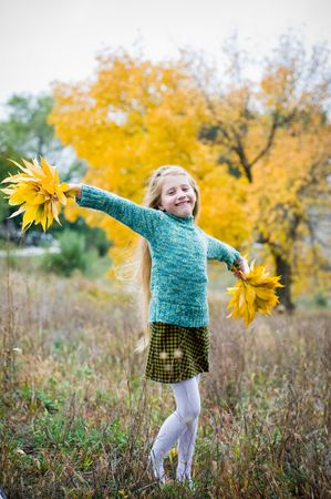 Cute girl with hands open over autumn background photo