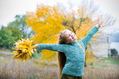 秋の背景上の手を持つ少女を開く
