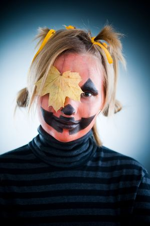 Smiling Jack-o-lantern girl with leaf on face photo