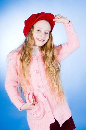 Smiling little girl in red cap, studio shot photo