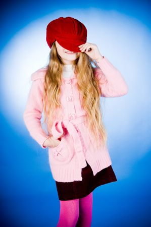 Funny little girl putting on red cap, studio shot photo