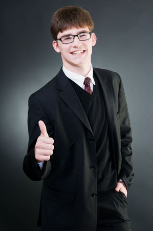 Young handsome businessman showing thumbs up, isolated on black background photo
