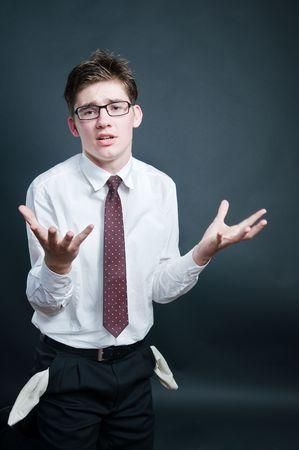 Upset businessman with empty pockets, isolated on black background