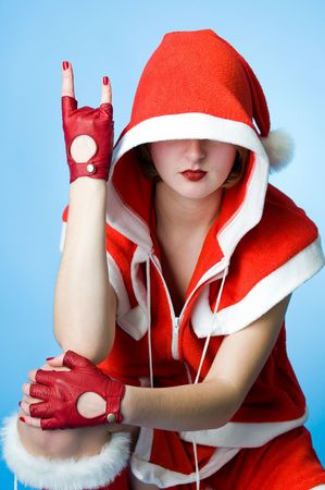 Cool girl in Santa Claus clothes over blue background