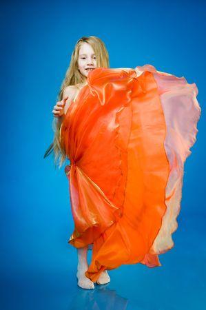 Cute little girl in orange dress over blue background  photo