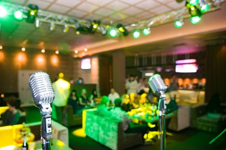 Close-up of retro microphone, blurred club interior with unrecognizable people on background