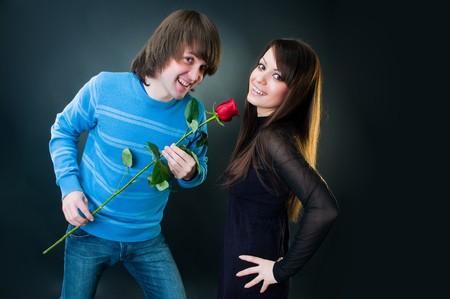 Romantic couple with rose, studio shot