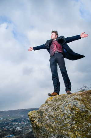 Stylish man with hands open over sky background  Standard-Bild
