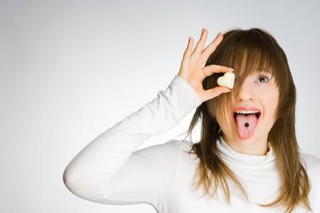 Screaming girl holding heart-shaped candy, studio shot