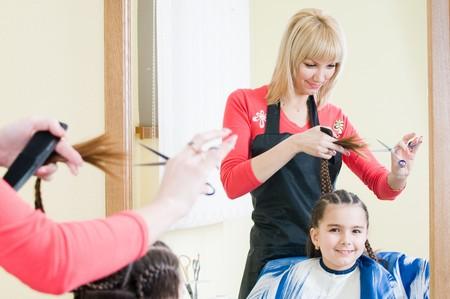 かわいい女の子美容サロンで彼女の新しい髪形を取得 写真素材