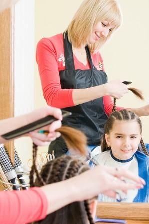 Bambina nel salone di parrucchiere, messa a fuoco selettiva Archivio Fotografico