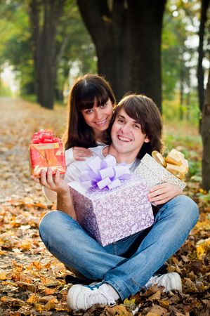 Young couple outside with gift boxes outside  photo