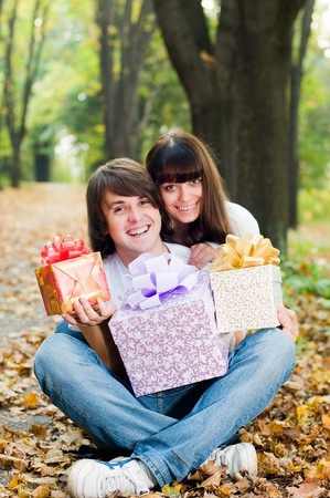 Young happy couple with gift boxes outside photo