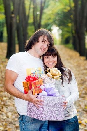 Young couple with gift boxes outside  photo