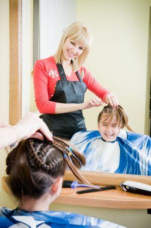 Cute little girl getting her new haircut in a barbershop photo