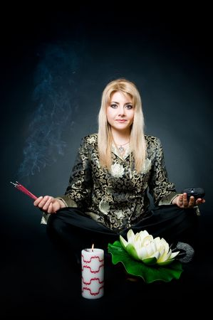 Woman meditating in lotus pose with aroma sticks, lotus, and candle   photo