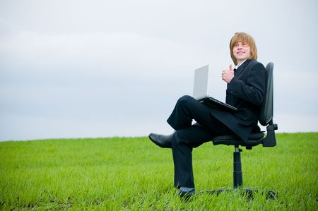 Handsome young businessman with laptop outdoors  photo