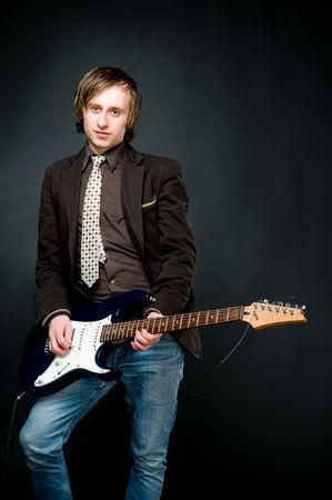 Young man playing electro guitar, studio shot   photo