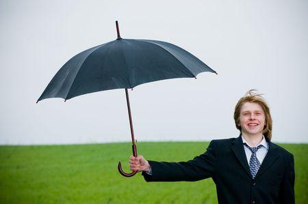 保護の概念の外の傘があるビジネスマンの笑みを浮かべてください。 写真素材