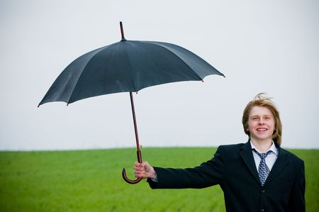 Smiling businessman with umbrella outside – protection concept