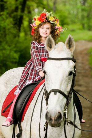 horse harness: Little girl in floral wreath riding horse in the forest  Stock Photo
