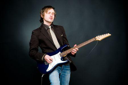 Man playing electro guitar, studio shot   photo