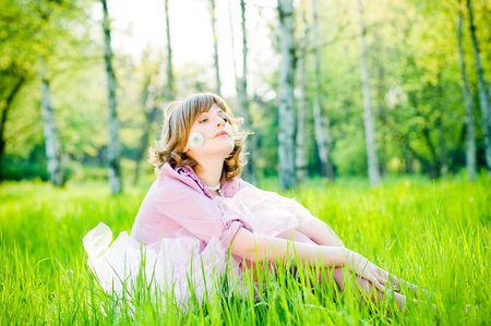 完璧な緑の草にタンポポと魅力的な女の子 写真素材