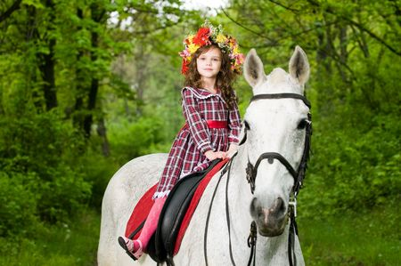 Little cute girl in floral wreath riding horse in the forest  Stockfoto