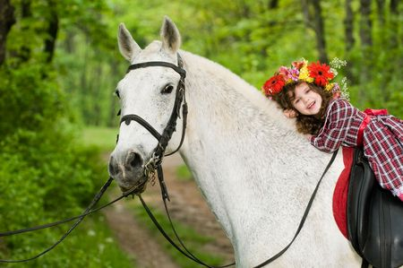 Smiling little girl in floral wreath riding horse in the forest  Standard-Bild