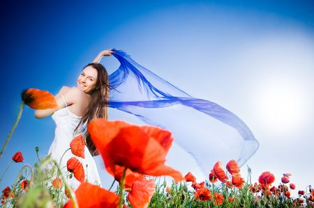 Beautiful girl in the poppy field, low angle view  Stockfoto