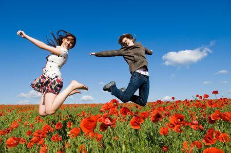 Beau jeune couple de sauter dans le champ de coquelicots, motion blur