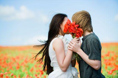novios besandose: Encantadora pareja bes�ndose en el campo de amapola