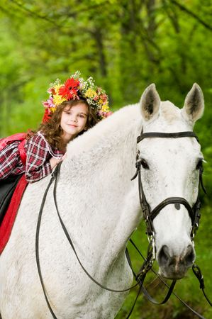 Cute little girl in floral wreath riding horse in the forest  Stockfoto