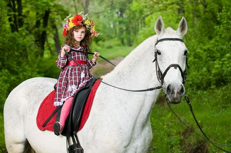 Little girl in floral wreath riding horse in the forest  Standard-Bild