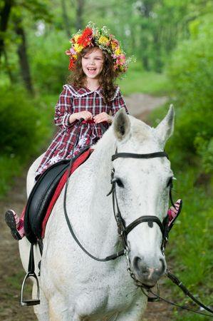 coronet: Laughing little girl in floral wreath riding horse in the forest  Stock Photo