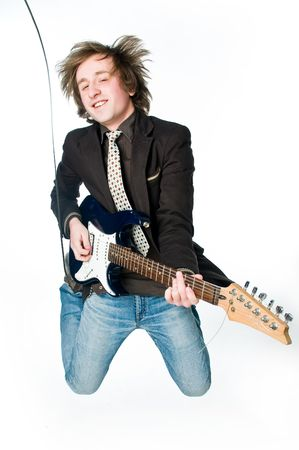 Young man jumping with electro guitar, motion blur