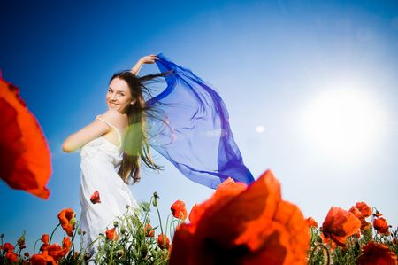 Attractive girl in the poppy field, low angle view  Standard-Bild