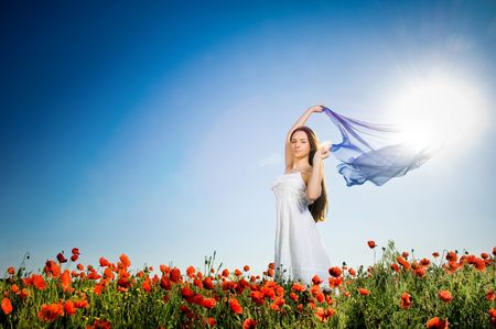 Beautiful girl in the poppy field, low angle view  photo