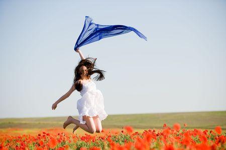 ケシ畑でジャンプ青いスカーフで美しい少女