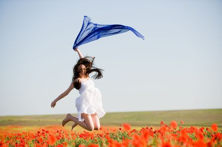 Beautiful girl with blue scarf jumping in the poppy field  Standard-Bild