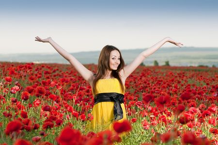Beautiful smiling girl in the poppy field   photo