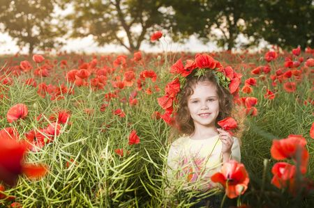 Smiling little girl with flowers in the poppy field   photo