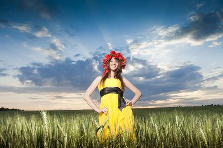 Beautiful young girl in floral wreath in the wheat field   photo