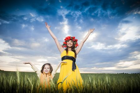 Beautiful mother and daughter in floral wreath in the wheat field   photo