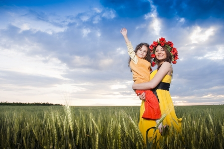 Beautiful mother and daughter in the wheat field   Standard-Bild