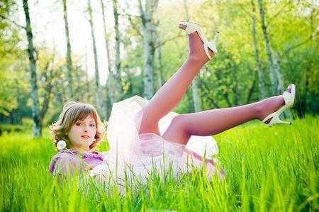 完璧な緑の草にタンポポで美しい少女