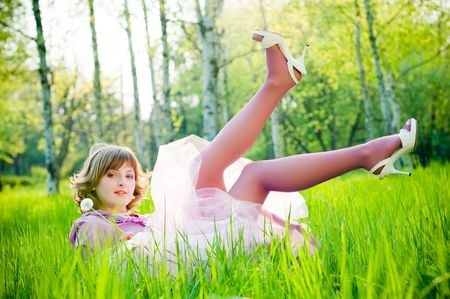 Beautiful girl with dandelion in perfect green grass