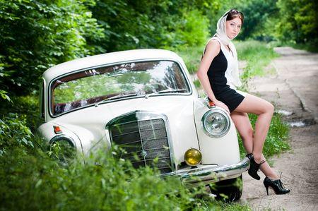 Beautiful pin-up styled girl sitting on retro car