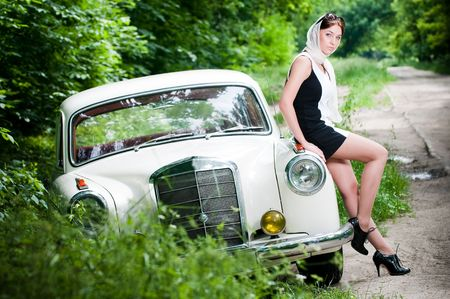 Beautiful pin-up styled girl sitting on retro car  photo