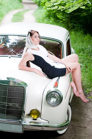Attractive pin-up girl sitting on retro car  photo